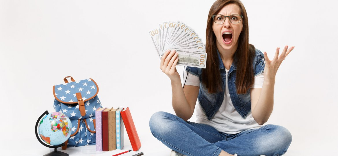 Young angry woman student screaming spreading hands holding bundle lots of dollars, cash money sit near globe backpack, books isolated on white background. Education in high school university college.